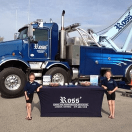 Young children standing next to Ross Towing And Transportation Services Inc table